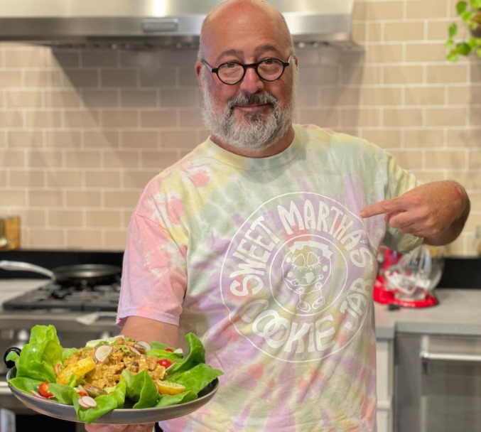 Andrew zimmern showing his dish
