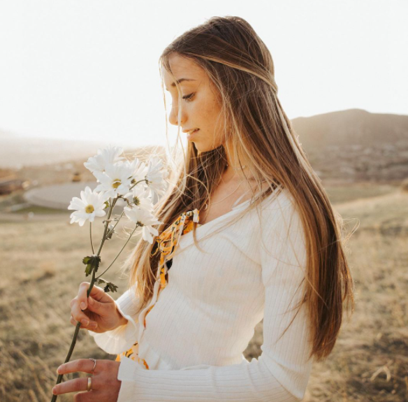 Brooklyn Mcknight holding white flowers in a white dress